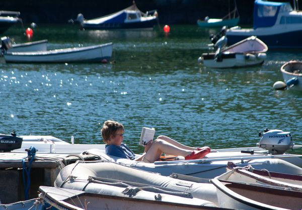 A boy reads whilst relaxing on a moored boat